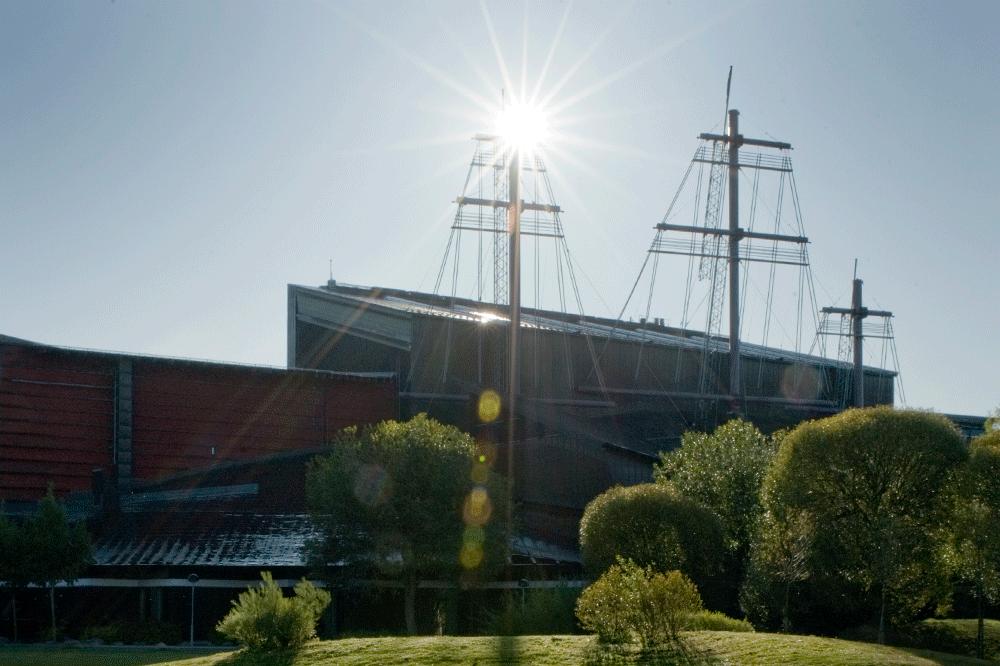 Vasamuseets byggnad. Gräsmatta och gröna träd framför. Bilden tagen i motljus.
